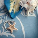 Σύνθεση με τα κοχύλια θάλασσας και έναν αστερία που τίθεται στις πετσέτες βαμβακιού Στοκ Εικόνες