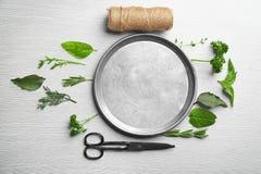Σύνθεση με τα φρέσκα χορτάρια και το μεταλλικό πιάτο Στοκ Εικόνες