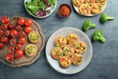 Σύνθεση με τα tartlets και τα λαχανικά πίτα μπρόκολου στοκ εικόνες