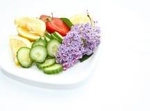 Σύνθεση με τις φέτες λεμονιών, τα αγγούρια, τη φράουλα και το ιώδες λουλούδι που απομονώνονται στο άσπρο υπόβαθρο με το διάστημα  Στοκ φωτογραφίες με δικαίωμα ελεύθερης χρήσης