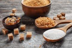 Σύνθεση με τους διαφορετικούς τύπους ζαχαρών στον ξύλινο πίνακα στοκ εικόνα