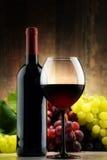 Σύνθεση με το γυαλί, το μπουκάλι του κόκκινου κρασιού και τα φρέσκα σταφύλια στοκ εικόνες με δικαίωμα ελεύθερης χρήσης