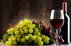 Σύνθεση με το γυαλί, το μπουκάλι του κόκκινου κρασιού και τα φρέσκα σταφύλια Στοκ Εικόνες