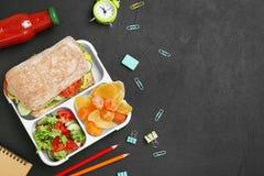 Σύνθεση με το καλαθάκι με φαγητό, τα ορεκτικά τρόφιμα και τα χαρτικά στο σκοτεινό υπόβαθρο, τοπ άποψη Στοκ Φωτογραφία