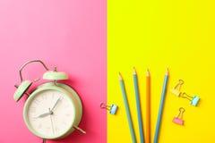 Σύνθεση με το ξυπνητήρι, τα μολύβια και τους συνδετήρες στο δίχρωμο υπόβαθρο στοκ εικόνες