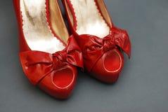 Σύνθεση μόδας: Κόκκινα κομψά παπούτσια, με τα μεγάλα τόξα κλείστε επάνω τα διαφορετικά τακούνια ποδιών κινηματογραφήσεων σε πρώτο στοκ φωτογραφία με δικαίωμα ελεύθερης χρήσης