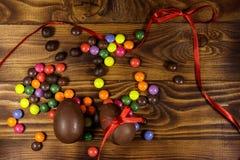 Σύνθεση Πάσχας με τα αυγά σοκολάτας στο ξύλινο υπόβαθρο Στοκ Φωτογραφία