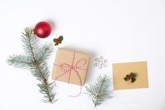 Σύνθεση πλαισίων Χριστουγέννων Δώρο Χριστουγέννων, κλάδος πεύκων, κόκκινες σφαίρες, φάκελος, άσπρα ξύλινα snowflakes, κορδέλλα κα Στοκ εικόνες με δικαίωμα ελεύθερης χρήσης