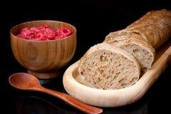 Σύνθεση στο μαύρο υπόβαθρο Ξύλινο πιάτο με το τεμαχισμένο ψωμί, στοκ φωτογραφία
