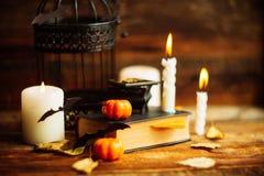 Σύνθεση του διακοσμητικών κρανίου, της κολοκύθας, των κεριών και των διακοσμήσεων αποκριών στον ξύλινο πίνακα, στο σκοτεινό υπόβα Στοκ Εικόνες