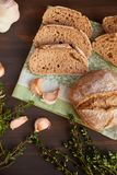 Σύνθεση του σκόρδου και του ψωμιού σε έναν σκοτεινό ξύλινο πίνακα Πρόσφατα ψημένο χειροποίητο ψωμί σε μια πετσέτα κουζινών Το ψωμ Στοκ εικόνα με δικαίωμα ελεύθερης χρήσης