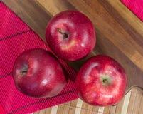 Σύνθεση τριών κόκκινων μήλων σε έναν ξύλινο πίνακα στοκ εικόνα