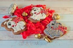 Σύνθεση τριών μπισκότων μελοψωμάτων στη μορφή των σκυλιών και των διακοσμήσεων Χριστουγέννων στον πίνακα Στοκ εικόνα με δικαίωμα ελεύθερης χρήσης