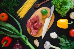 Σύνθεση τροφίμων με το κρέας στον ξύλινους πίνακα, το μαχαίρι, τα ζυμαρικά και τα λαχανικά στο σκοτεινό πίνακα Τοπ όψη Επίπεδος β Στοκ Εικόνες
