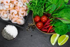 Σύνθεση τροφίμων των λαχανικών και των καρυκευμάτων γαρίδων στο μαύρο υπόβαθρο πετρών στοκ εικόνα