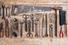 Σύνθεση των εργαλείων κατασκευής σε μια παλαιά χτυπημένη ξύλινη επιφάνεια των εργαλείων: πένσες, γαλλικό κλειδί σωλήνων, κατσαβίδ Στοκ φωτογραφία με δικαίωμα ελεύθερης χρήσης