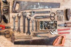 Σύνθεση των εργαλείων κατασκευής σε μια παλαιά χτυπημένη ξύλινη επιφάνεια των εργαλείων: πένσες, γαλλικό κλειδί σωλήνων, κατσαβίδ Στοκ Εικόνες