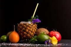 Σύνθεση των θερινών φρούτων Ζωηρόχρωμα εσπεριδοειδή και ένα φλυτζάνι ανανά Γρανάτης, αβοκάντο, καρύδα και carambola στο Μαύρο Στοκ Εικόνα