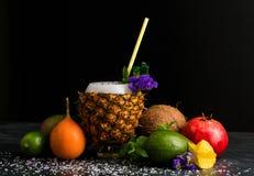 Σύνθεση των θερινών φρούτων Ζωηρόχρωμα εσπεριδοειδή και ένα φλυτζάνι ανανά Γρανάτης, αβοκάντο, καρύδα και carambola στο Μαύρο Στοκ εικόνες με δικαίωμα ελεύθερης χρήσης