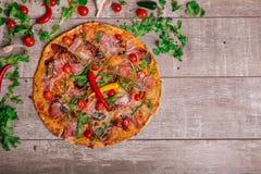Σύνθεση των ιταλικών τροφίμων Λαχανικά και πίτσα σε ένα καφετί υπόβαθρο Ιταλική πίτσα με το καυτό πιπέρι και την πικάντικη σάλτσα Στοκ φωτογραφίες με δικαίωμα ελεύθερης χρήσης