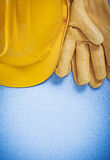 Σύνθεση των κίτρινων σκληρών προστατευτικών γαντιών καπέλων στο μπλε backgro Στοκ φωτογραφίες με δικαίωμα ελεύθερης χρήσης