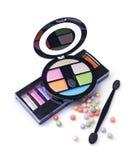 Σύνθεση των καλλυντικών με τις χρωματισμένες σκιές ματιών, τις σφαίρες σκονών προσώπου και applicators Στοκ Εικόνες