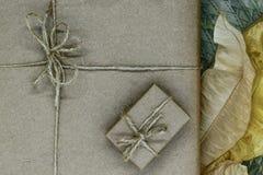 Σύνθεση των κιβωτίων δώρων που τυλίγονται στο μπεζ έγγραφο και που συσσωρεύονται με τις κορδέλλες Διακοσμημένος με τα ξηρά φύλλα στοκ εικόνες