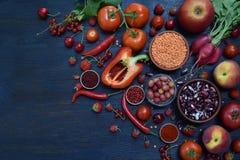 Σύνθεση των κόκκινων χορτοφάγων προϊόντων: φρούτα, λαχανικά, καρυκεύματα και φασόλια στο ξύλινο υπόβαθρο Ντομάτες της Apple, πιπέ Στοκ Φωτογραφία
