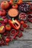 Σύνθεση των κόκκινων χορτοφάγων προϊόντων: φρούτα, λαχανικά, καρυκεύματα και φασόλια στο ξύλινο υπόβαθρο Ντομάτες της Apple, πιπέ Στοκ εικόνα με δικαίωμα ελεύθερης χρήσης