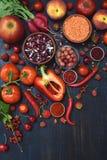 Σύνθεση των κόκκινων χορτοφάγων προϊόντων: φρούτα, λαχανικό και φασόλι στο ξύλινο υπόβαθρο Apple, ντομάτα, σταφίδα, ραδίκι, πιπέρ Στοκ Εικόνα