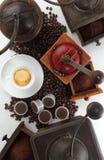 Σύνθεση των μύλων για τον καφέ με το φλυτζάνι, τα φασόλια και τις κάψες Στοκ Εικόνες