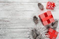 Σύνθεση των Χριστουγέννων, υπόβαθρο δώρων που συσκευάζεται στην κόκκινη συσκευασία με τους ζωηρόχρωμους διακοσμητικούς κώνους πεύ Στοκ Εικόνες
