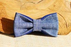 Σύνθεση: Υπερβολικός μπλε δεσμός τόξων και ξύλινη καμπύλη ραβδιών σε ένα μπεζ υπόβαθρο στοκ φωτογραφία