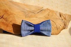 Σύνθεση: Υπερβολικός μπλε δεσμός τόξων και ξύλινη καμπύλη ραβδιών σε ένα μπεζ υπόβαθρο στοκ εικόνα με δικαίωμα ελεύθερης χρήσης