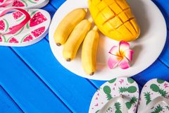 Σύνθεση φρούτων μάγκο μπανανών σε ένα μπλε ξύλινο υπόβαθρο Στοκ Φωτογραφίες
