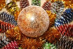 Σύνθεση Χριστουγέννων από τους χρωματισμένους κώνους έλατου, tinsel και έναν λαμπρό στοκ εικόνα με δικαίωμα ελεύθερης χρήσης