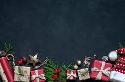 Σύνθεση Χριστουγέννων διακοσμήσεις στις μαύρες υποβάθρου Χριστουγέννων, κιβώτια, κλάδοι του δέντρου, ΚΑΠ, Santa, αστέρι Στοκ Φωτογραφία