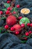Σύνθεση Χριστουγέννων με τον ελαιόπρινο, τις σφαίρες διακοπών και το κερί στο σκοτεινό υπόβαθρο, κατακόρυφος, διάστημα αντιγράφων Στοκ Εικόνες