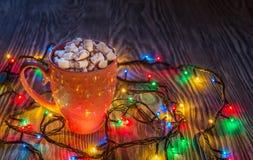 Σύνθεση Χριστουγέννων με το φλυτζάνι του κακάου και marshmallows και lig Στοκ φωτογραφία με δικαίωμα ελεύθερης χρήσης