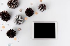 Σύνθεση Χριστουγέννων ταμπλετών για το χρόνο Χριστουγέννων κώνοι και διακοσμήσεις Χριστουγέννων στο άσπρο υπόβαθρο Στοκ φωτογραφία με δικαίωμα ελεύθερης χρήσης