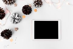 Σύνθεση Χριστουγέννων ταμπλετών για το χρόνο Χριστουγέννων κώνοι και διακοσμήσεις Χριστουγέννων στο άσπρο υπόβαθρο Στοκ Εικόνες