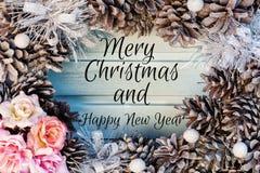 Σύνθεση Χριστουγέννων των κώνων και των λουλουδιών Όμορφο εορταστικό στεφάνι, η επιγραφή στο κέντρο της Χαρούμενα Χριστούγεννας στοκ εικόνα