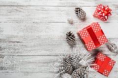 Σύνθεση Χριστουγέννων, υπόβαθρο δώρων που συσκευάζεται στην κόκκινη συσκευασία με τους χρωματισμένους διακοσμητικούς κώνους πεύκω Στοκ Φωτογραφία