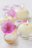 Σύνθεση SPA με το αλατισμένο λουτρό θάλασσας στο ξύλινο κουτάλι, τα ρόδινα λουλούδια και τα καίγοντας κεριά σε μια άσπρη επιφάνει Στοκ Εικόνες
