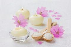 Σύνθεση SPA με το αλατισμένο λουτρό θάλασσας στο ξύλινο κουτάλι, τα ρόδινα λουλούδια και τα καίγοντας κεριά σε μια άσπρη επιφάνει Στοκ Εικόνα