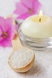 Σύνθεση SPA με το αλατισμένο λουτρό θάλασσας στο ξύλινο κουτάλι, τα ρόδινα λουλούδια και τα καίγοντας κεριά Στοκ φωτογραφία με δικαίωμα ελεύθερης χρήσης