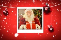 Σύνθετη εικόνα Άγιου Βασίλη που προσφέρει ένα κόκκινο δώρο στοκ φωτογραφίες