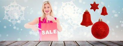 Σύνθετη εικόνα μοντέρνου ξανθού στο κόκκινο φόρεμα που παρουσιάζει τσάντα πώλησης Στοκ Εικόνα