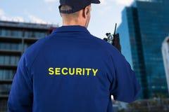 Σύνθετη εικόνα οπισθοσκόπου του αξιωματικού ασφαλείας που μιλά στην ομιλούσα ταινία walkie Στοκ Φωτογραφία