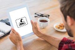 Σύνθετη εικόνα οπισθοσκόπου του ατόμου που χρησιμοποιεί την ταμπλέτα στον ξύλινο πίνακα Στοκ Φωτογραφία